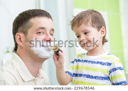 preschooler kid boy watching shaving of his dad - stock photo
