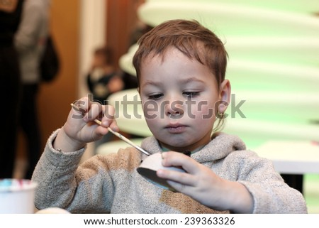 Preschooler paints a cardboard toy in the classroom - stock photo