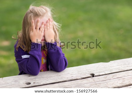 Preschooler playing game of hide and sick. Right now she is sitting on the table covering her eyes while taking a sneaky peek. - stock photo