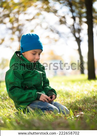 Preschooler with a sad expression on his face sitting on green grass on a blurred background - stock photo
