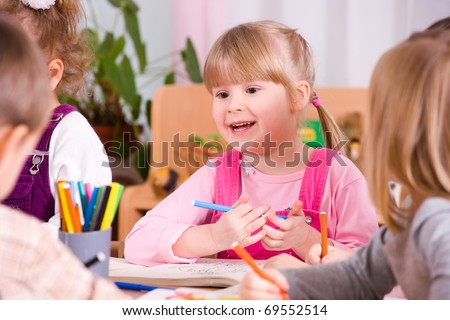 preschoolers playing and painting with colored pencils - stock photo