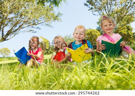 Preschoolers with books outside - stock photo