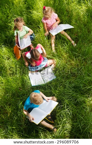 Preschoolers with books sitting on the grass - stock photo