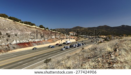 Prescott, Arizona, USA, March 5, 2015 Cars stopped at traffic light traveling on Highway 69 in Prescott, Arizona with mountains in background