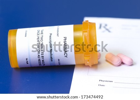 Prescription bottle, pink pills, and prescription pad on royal blue background. - stock photo