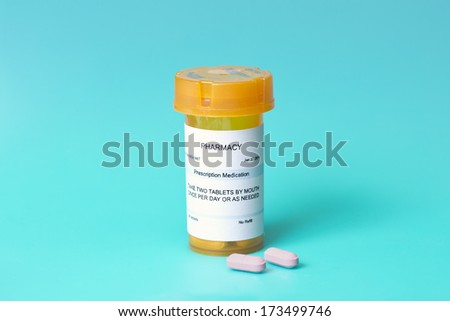 Prescription bottle, pink pills on blue background. - stock photo