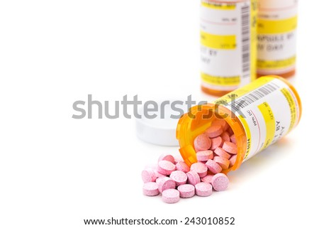 Prescription medication cascading out of orange pharmacy vials isolated on white - stock photo