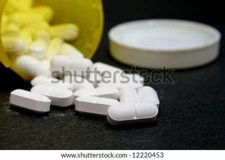 Prescription Medication, white tablets spilling out of a pharmacy bottle - stock photo