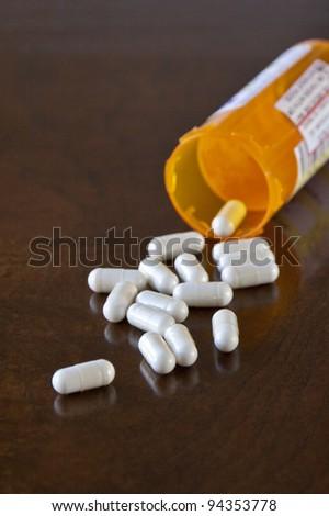 Prescription medicine pills pouring out of orange bottle on a table. selective focus - stock photo