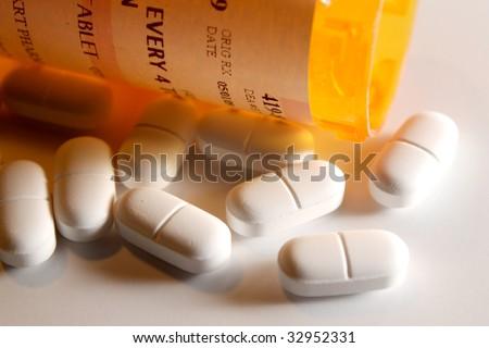 Prescription Pain Pills spilling out of a bottle - stock photo