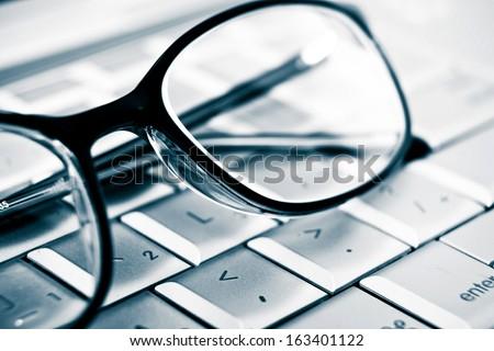 Prescription vision glasses on an aluminum laptop. Detail. Modern technology concept - stock photo