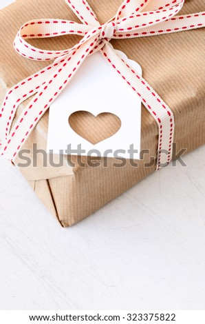 Present box tied with bow with heart gift tag, birthday christmas valentines day special occasion - stock photo