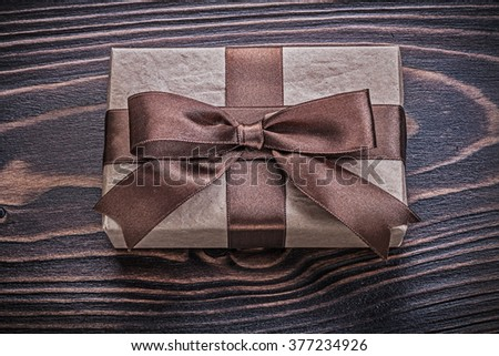 Present box with brown bow on wooden board holidays concept. - stock photo