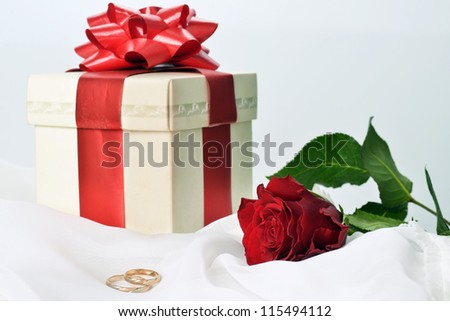 Present box with rose on white silk