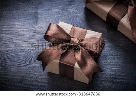 Present boxes with tied ribbons on wood board holiday concept.