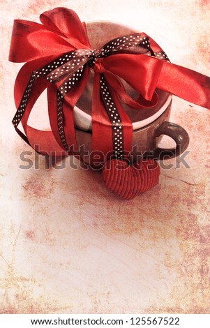 Present cup with a red  ribbon bow with heart for Valentine's day/vintage valentine background