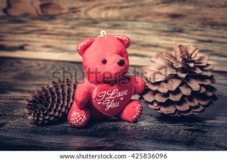 Present from forest. Two big fir cones and red bear with heart.Love and bear. - stock photo