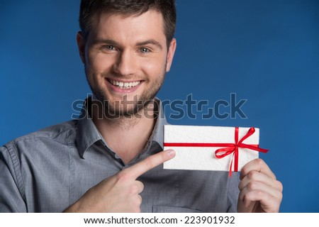Present gift in hands of smiling man. closeup on happy man standing on blue background and pointing