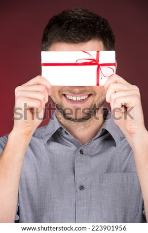 Present gift in hands of smiling man. closeup on happy man standing on red background - stock photo