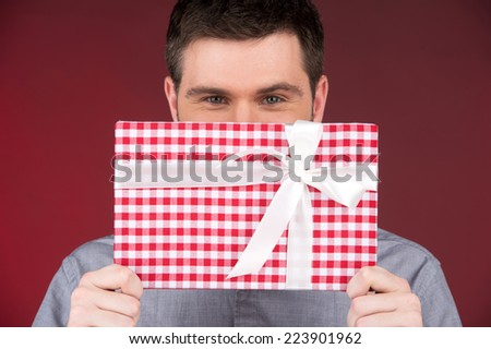 Present gift in hands of smiling man covering half face. closeup on happy man standing on red background - stock photo