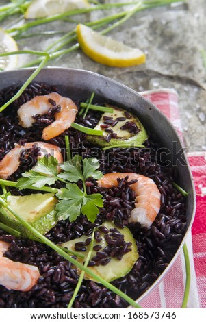 Presentation and preparation of black rice with zucchini and shrimps
