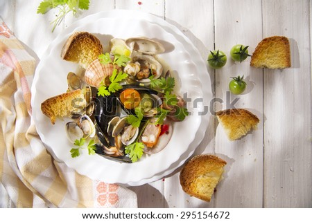 Presentation of a soup with seafood with roasted bread - stock photo