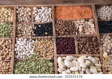 Presentation of mixed seeds of pulses in a display of wood - stock photo