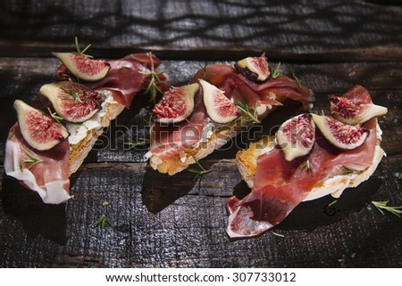 Presentation on wooden table bruschetta with figs and prosciutto - stock photo