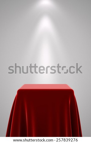 Presentation pedestal covered with a red silk cloth in front of a white wall illuminated by a spot light - stock photo