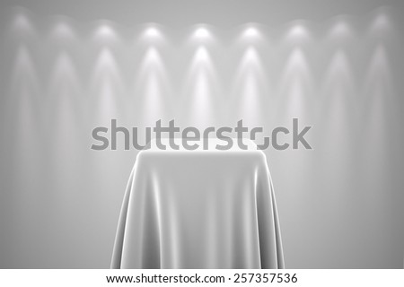 Presentation pedestal covered with a white  silk cloth in front of a wall illuminated by a spot light - stock photo