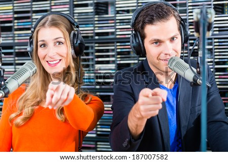 Presenters or moderators - man and woman - in radio station hosting show for radio live in Studio - stock photo