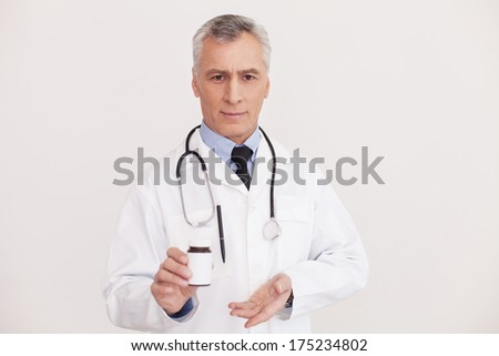 Presenting brand new medicines. Senior grey hair doctor in uniform pointing a medicine bottle and looking at camera while standing isolated on white