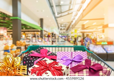 presents ribbon gift box in shopping trolley in shopping mall background.  - stock photo