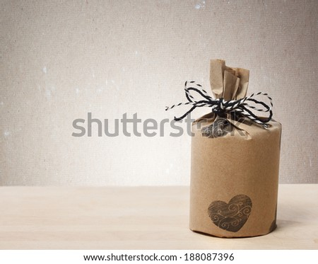Presents wrapped in a rustic earthy style on beige paper background - stock photo