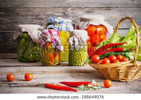 Preserved and fresh vegetables on wooden background - stock photo