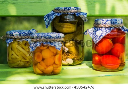 Preserved asparagus beans, apricots, cucumbers, tomatoes in glass jars on green wooden background - stock photo