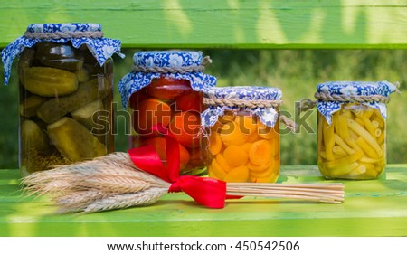 Preserved asparagus beans, apricots, cucumbers, tomatoes in glass jars with bunch of wheat ears on green wooden background - stock photo