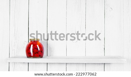 Preserved food in glass jar, on a wooden shelf. Marinaded a strawberry - stock photo