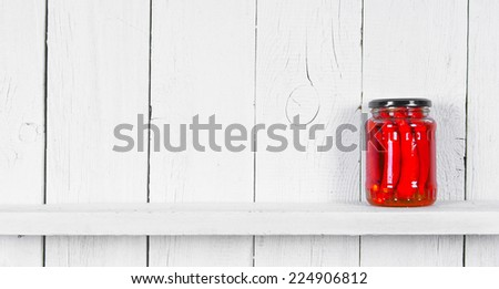 Preserved food in glass jar, on a wooden shelf. Marinaded hot pepper - stock photo