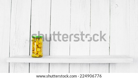 Preserved food in glass jar, on a wooden shelf. Marinaded mushrooms - stock photo
