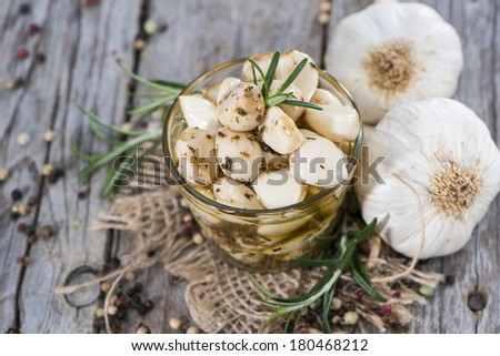Preserved Garlic with fresh herbs on vintage background - stock photo