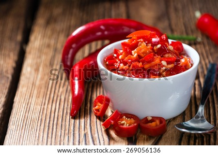 Preserved red Chilis (close-up shot) on wooden background - stock photo