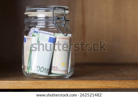 preserving glass with Euro banknotes in a wooden shelf, financial concept for saving money - stock photo