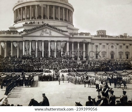 President Roosevelt taking the oath of office, Mar. 4 1905. The east portico of the U.S. Capitol is decorated with flags and masses of people crowd its roofs and balconies. - stock photo