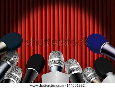 Press conference with microphones over red curtain - stock photo