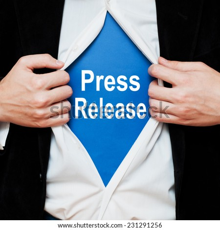 Press Release. Businessman showing a superhero suit underneath his shirt with a message text written on it. - stock photo