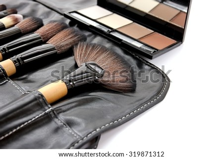 Pressed powders and makeup brushes on white background. - stock photo