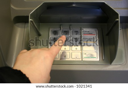 pressing personal code at ATM machine (focus on finger)