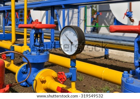 Pressure meter and red faucet with steel yellow pipe in natural gas treatment plant in bright sunny summer day - stock photo