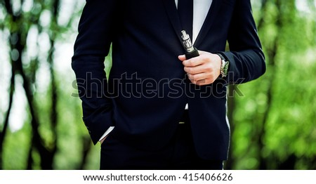 prestigious man in an expensive black suit, tie and white shirt holding an electronic cigarette in their hands. the concept of health, advanced technologies. - stock photo
